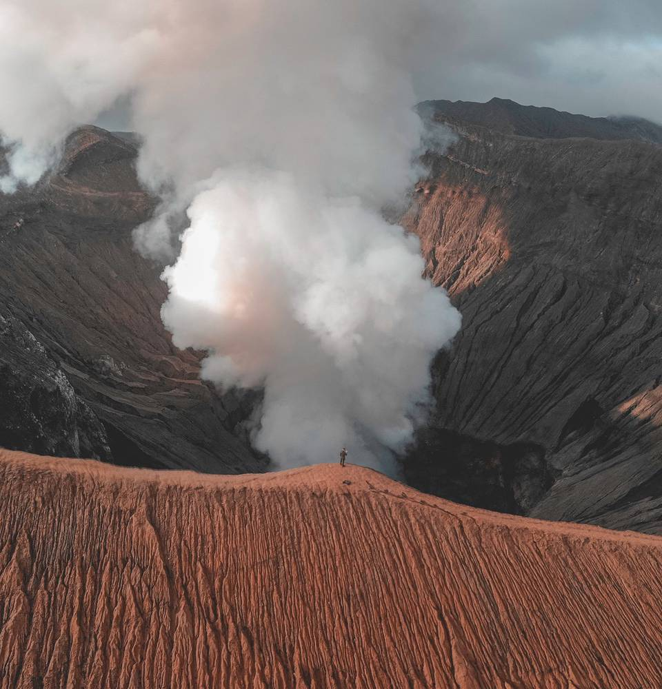 Mount Bromo in Indonesia after night hike with active vulcano gas erupting