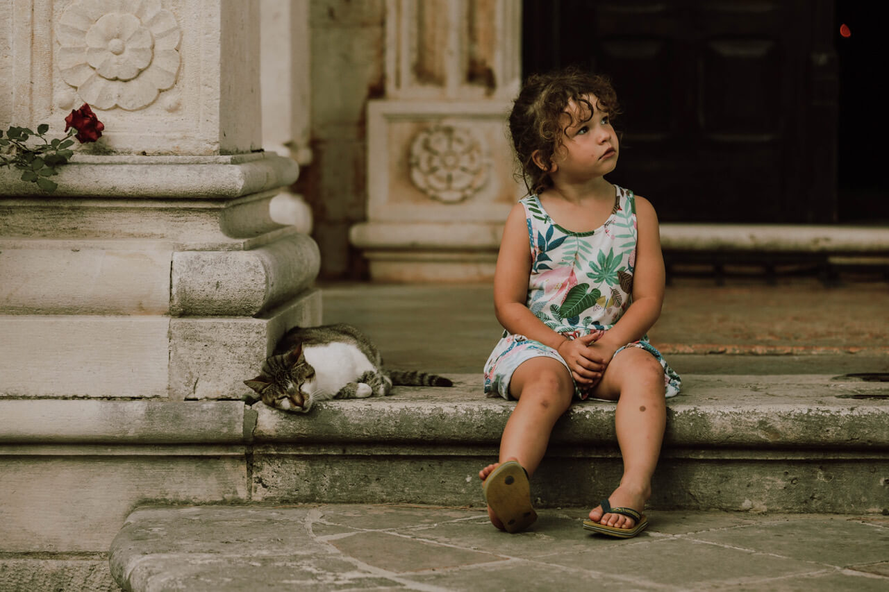 Girl sitting next to a sleeping cat before a church