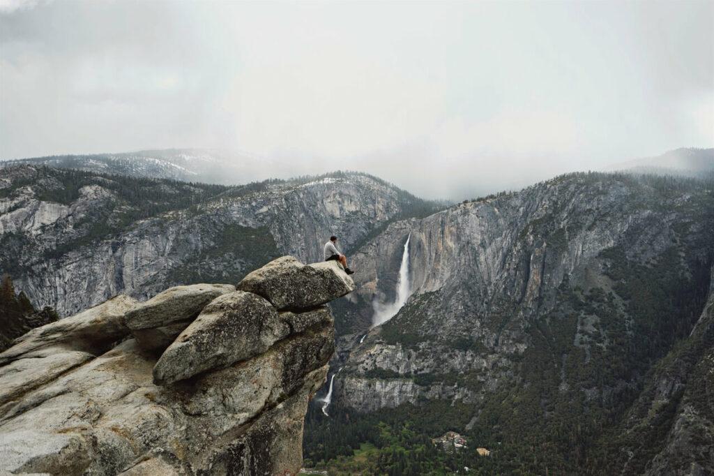 man sitting on rock watching a huge waterfall far away, walden and Jack Wolfskin
