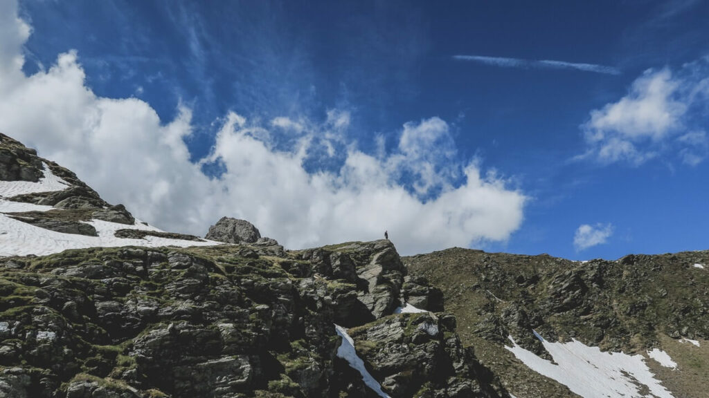 man standing in teh Austrian Alps on a rocky mountain with blue sky and snow on its hills