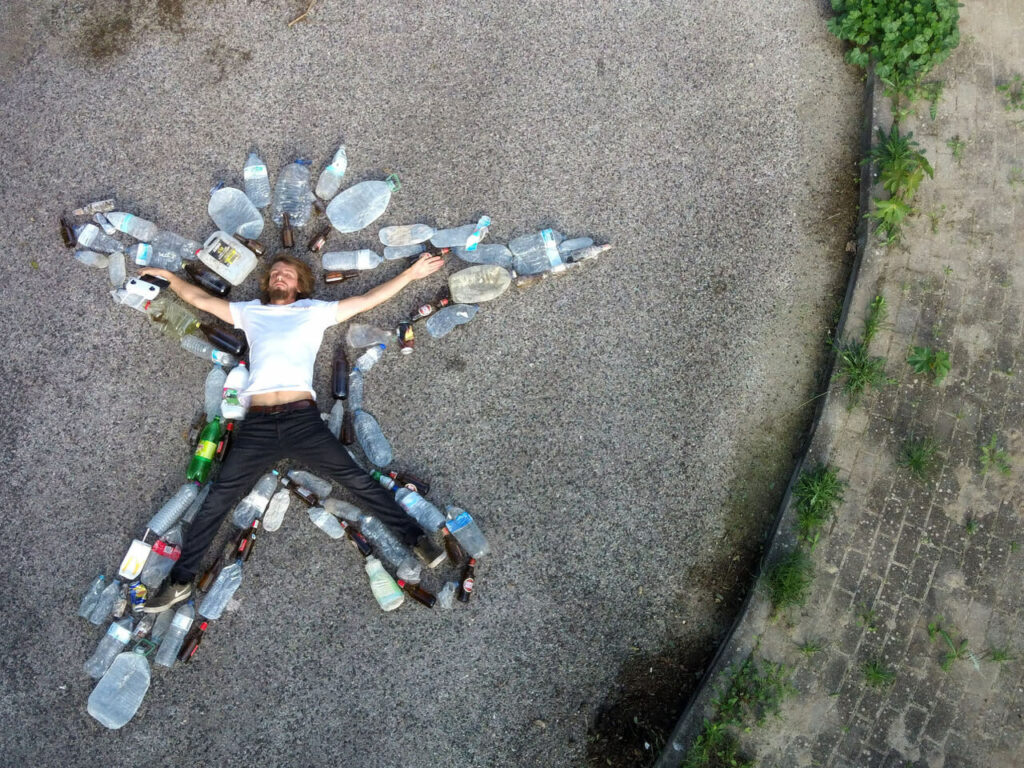 The Trash Traveller surrounded with plastic bottles