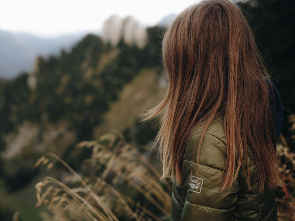 woman looking into a valley with olive green Jack Wolfskin mountain jacket