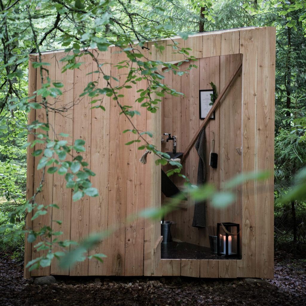 wooden outdoor bathroom with open door and candle Stedsans JW