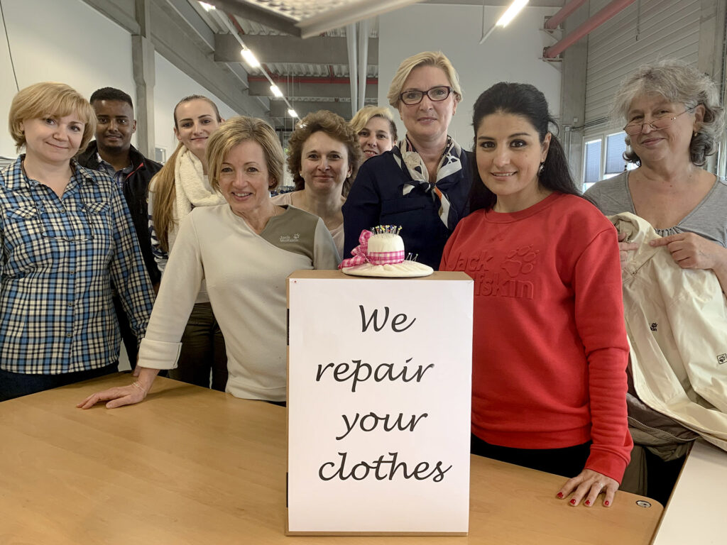 staff and team at Jack Wolfskin with a we repair your clothes sign
