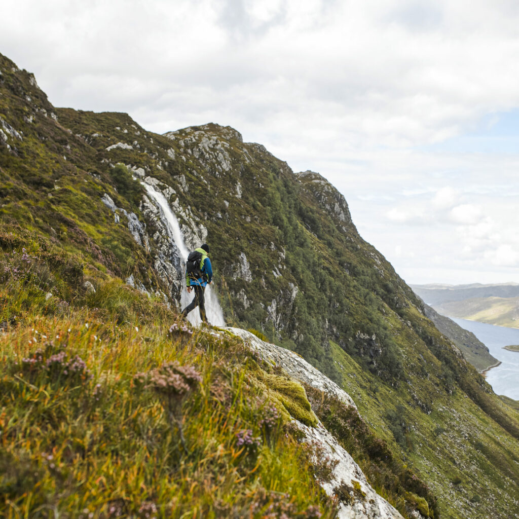 Man walking on a mountain path next to a water fall