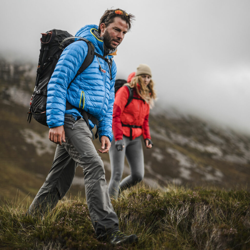 German borne mountain guide Ben wearing a blue Jack Wolfskin jacket, behind him a woman with a red JW jacket