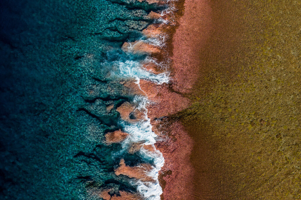 birds view of the beautiful pacific ocean hitting a reddish rock formation