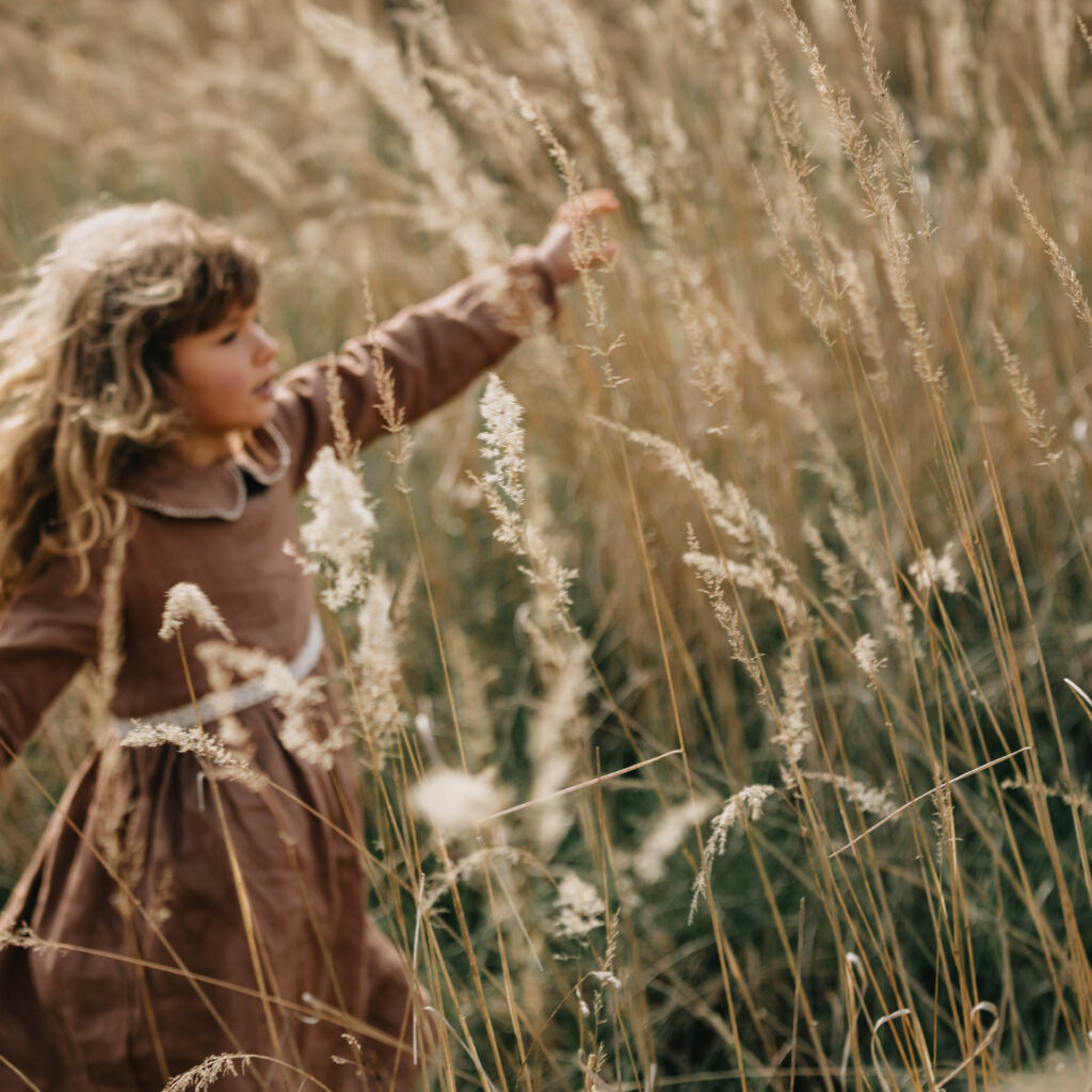 girl in a field with wind blowing