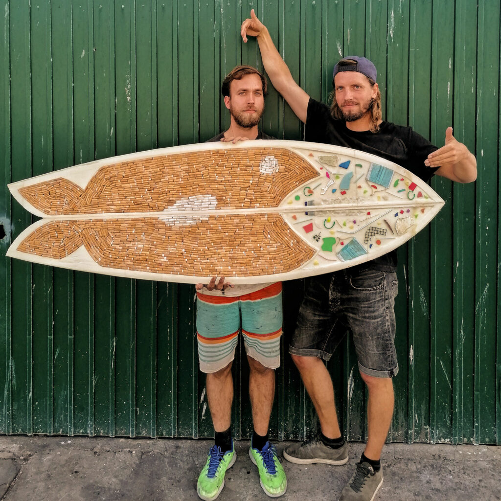two artists and a surf board made from trash
