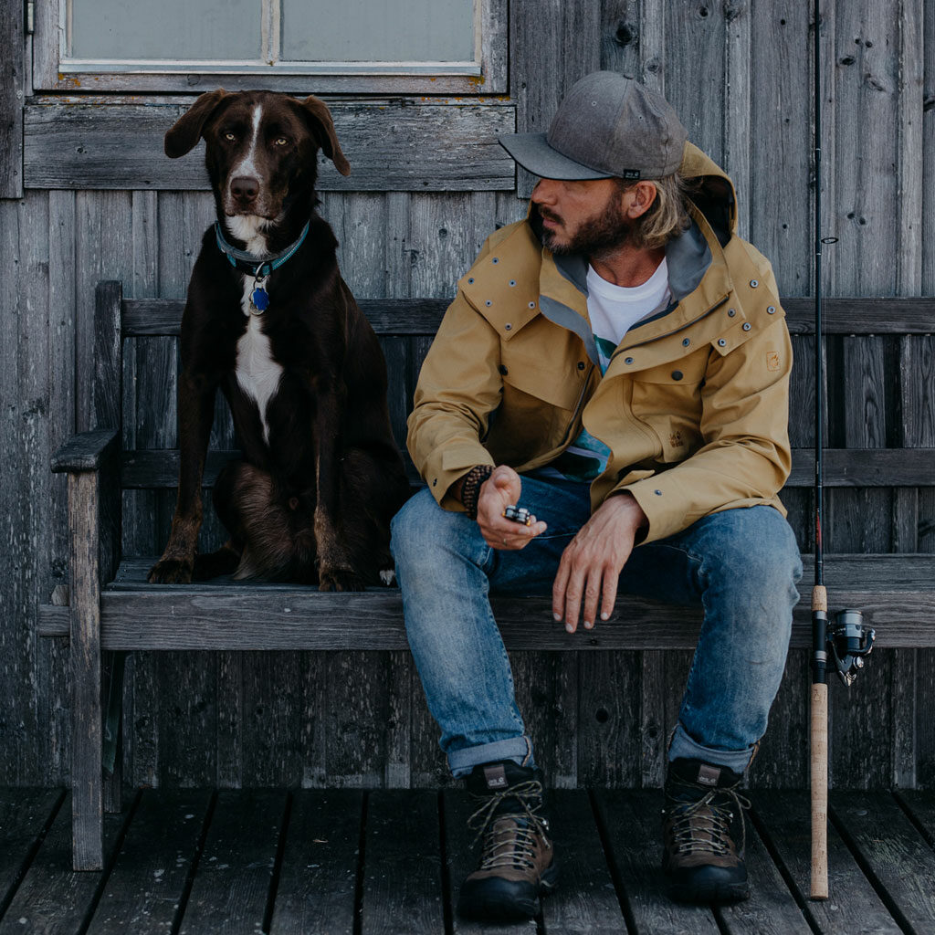 Fotografer Guerel Sahin with his dog sitting on a bench, a fishing rod is just nearby