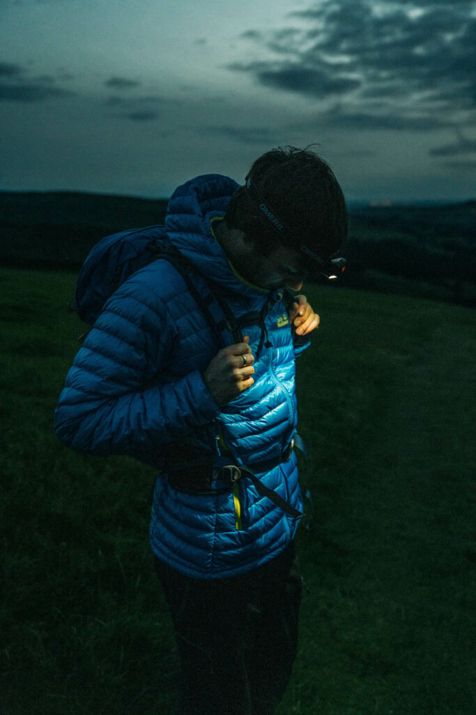 night hiking with head lamp and a blue Jack Wolfskin Jacket