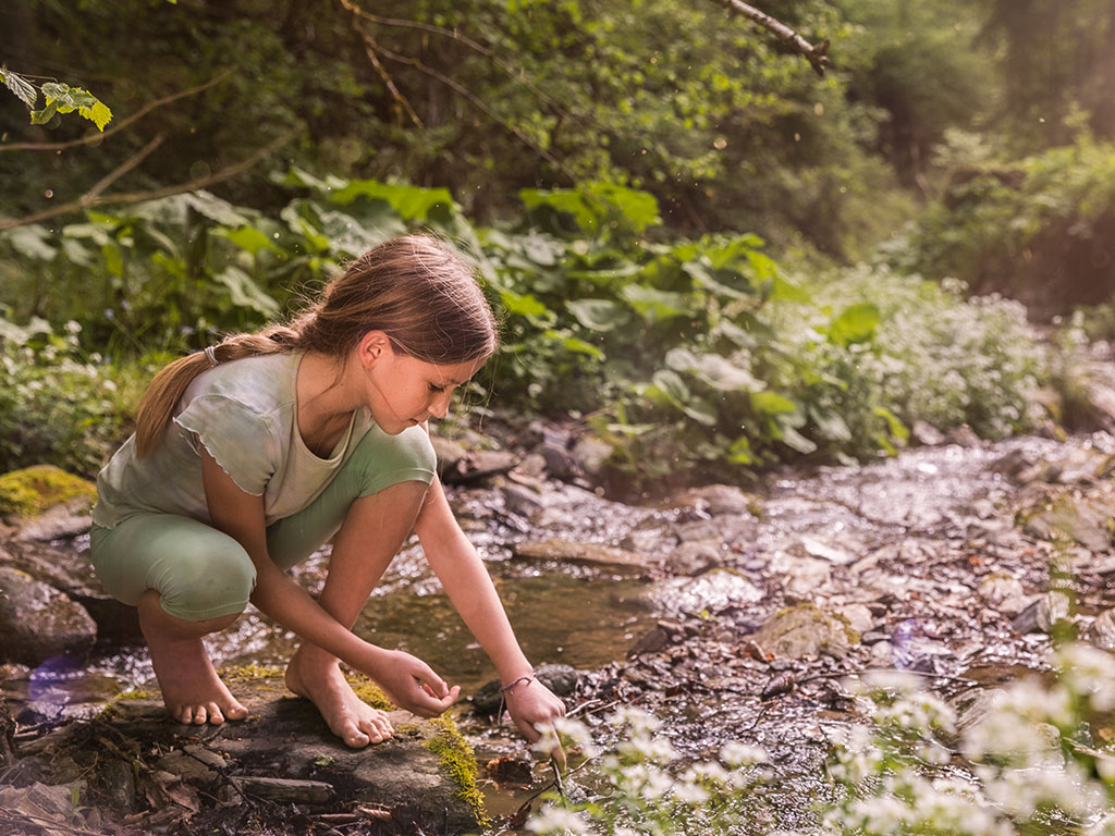 summer time, a girl is standing barefoot beside a stream of water, kids enjoy discovering nature, while parents bond with them
